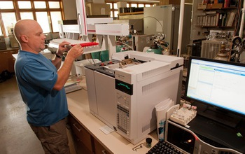 LTER scientist Kevin Kahmark next to equipment analyzing samples in the lab.