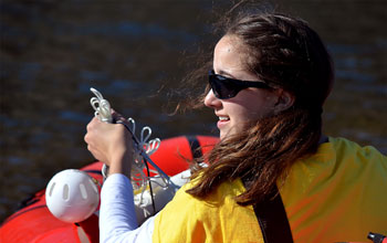 Photo of student Marisa LaRouche sampling water in a Greenland lake.