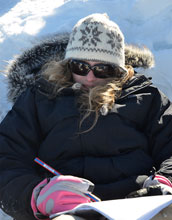 Photo of student Alexandra Schmidt taking notes during an experiment on the Greenland Ice Sheet.
