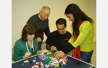 Photo of a a team working on one of the tasks used in the study involving Legos.