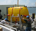 Photo of autonomous underwater vehicle Sentry being loaded onto a vessel.