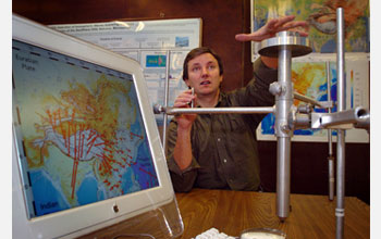 Geophysicist Eric Calais holds a geodetic marker that tracks even very small Earth movements.