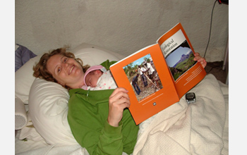 Photo of Starry Sprenkle viewing her first publication with her first child.