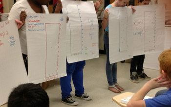 Middle school students holding sheets during a presentation