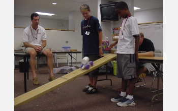 Students watch as robot rolls down plank.