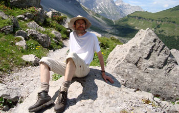Photo of Thomas DeGrand sitting on a rock in a scenic, mountainous area
