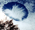 Above Alabama, hole-punch clouds dot the sky.