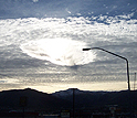 Hole-punch clouds seem to touch a streetlight in Washington State.