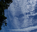 Hole-punch clouds appear over Norfolk, Va., with aircraft contrails leading from them.