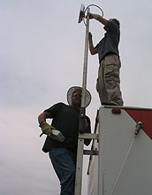 Two men work on a communications antenna.
