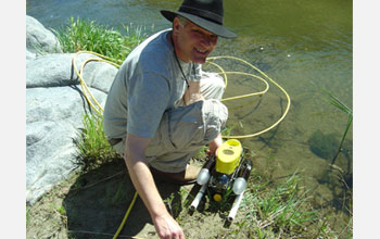Photo of Hans-Werner Braun deploying a sensor-equipped autonomous underwater vehicle into a stream.