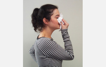 Photo of a woman blowing her nose into tissue.