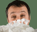 Photo of a man with a cold with a pile of tissues in front of him.