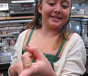 Photo of a girl holding a grasshopper at ASU's STEM Summer College-for-Kids.