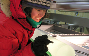 Photo of a researcher inspecting a freshly-drilled ice core.
