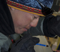 Photo of a researcher examining an ice core.