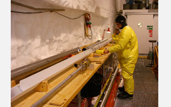 Photo of a person pushing an ice core out of the drill.