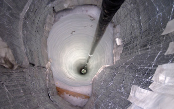 Photo of a sensor descending down a hole in the ice as part of the final season of IceCube.