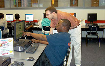 Photo of Dan DuBrow assisting a student who is remotely accessing radiation equipment.