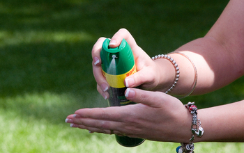 person spraying insect repellant on hands