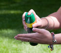 woman spraying insect repellant on hands