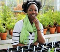 Lekeah A. Durden in a greenhouse with plants