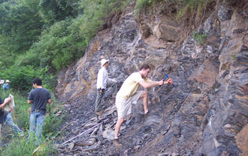 Photo of geologists digging into a shale exposure in north China.