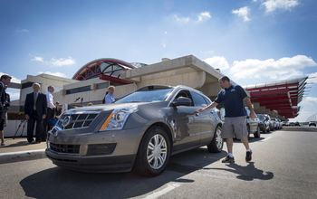 People standing next to parked Cadillac SRX  driverless car