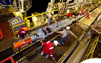 Image of JOIDES Resolution crew members prepping a CORK for installation beneath the seafloor.