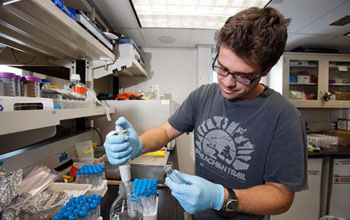 Image of microbiologist Joe Russell examining samples in the lab onboard the JOIDES Resolution.