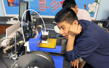 Buford Middle School student watches a 3-D printer at work