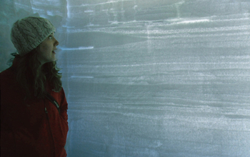 Kaitlin Keegan in a snow pit on the Greenland ice sheet. The pit shows layers of accumulation.