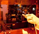 Photo of researcher loading a template used for nano-sculpting on plastic films.