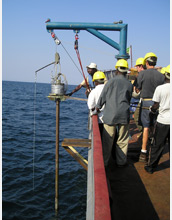 A sediment core is collected from the side of a vessel.
