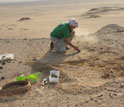 Photo of paleontologist Erik Seiffert excavating a new location in Egypt's Fayum Depression.