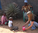Scientist Kathleen Alexander with locals in a yard in a Botswana village.