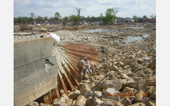 Researchers inspect a portion of the floodwall that was overtopped and flattened.