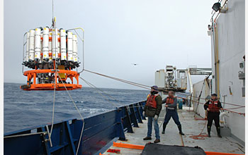 "Photo of 3 crew members, ""tag lines"" and equipment on the ship's deck."
