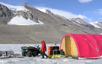 Researcher at Antarctica's Dry Valleys LTER Site, with tent and equipment
