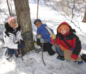 "Three young ecology students with a ""camera trap"" in the woods."