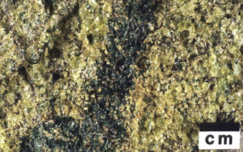 Detailed photo of peridotite, a pale green olive-colored rock