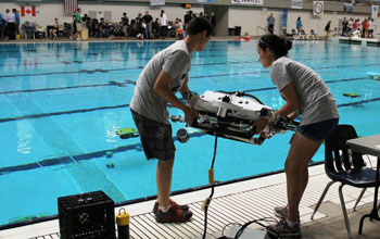 Team members standin next to a pool preparing to launch  their project