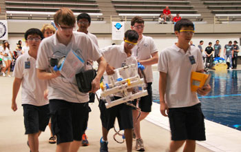 Students walking back with their remote underwater vehicles