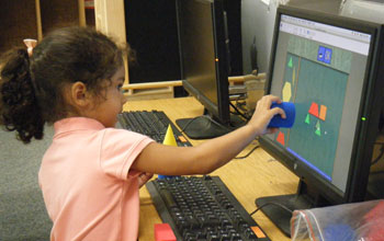 Photo of a girl using a computer to match shapes to build pictures.