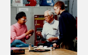 Students and a professor discuss engineering concepts during a Learning Factory exercise.