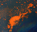Photo of oil slick at the sea's surface containing orange-colored older oil and fresher oil sheen.