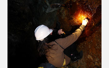 Photo of a  researcher collecting a sample at a mine for microbial analysis.