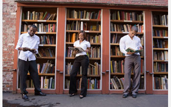 Photo of three African American students reading in front of a bookshelf.