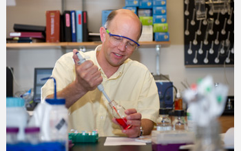 Photo of Nicholas Hud extracting a study sample in his laboratory.
