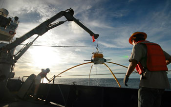 Marine scientists on a ship at sea hauling in an electromagnetic receiver.